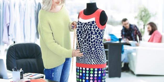 Kreatywny krawiec pracujący nad krawiectwem modnej sukienki