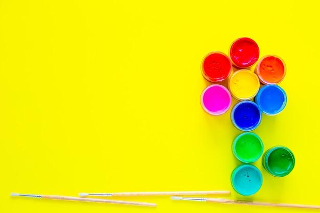 Kreatywny kwiatek złożony z puszek po farbie i pędzli do rysowania pod nim na żółtym tle...