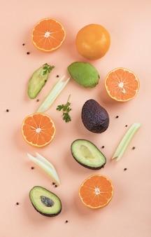 Kreatywny letni wzór z pomarańczy i selera oraz awokado na pomarańczowym tle. minimalna koncepcja owoców. leżał na płasko.