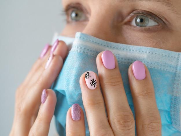 Kreatywny manicure z malowanym koronawirusem na paznokciach, nieostrość, zbliżenie