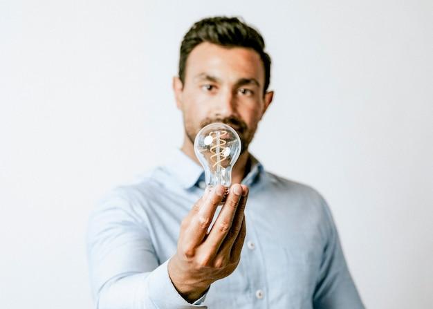 Kreatywny mężczyzna trzymający żarówkę