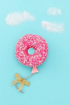 Kreatywny minimalizm żywności. pączek na błękitnym tle, pączek w kształcie balonu na niebie, odgórny widok