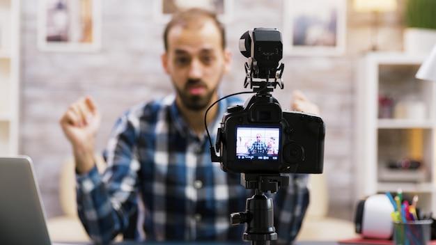 Kreatywny młody człowiek rozmawia przed kamerą. powiększenie efektu strzału.