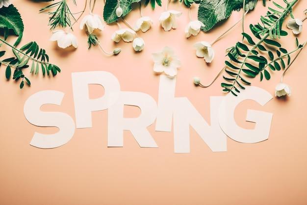 Kreatywny napis wiosna z kwiatami i liśćmi