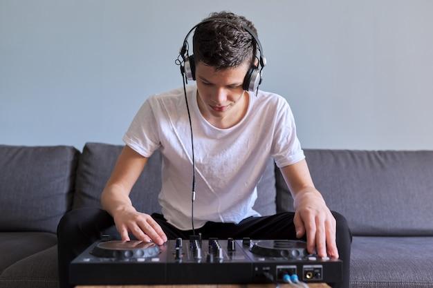 Kreatywny nastolatek w słuchawkach z mikserem stacja rozrywkowa dj, nastolatek zainteresowany muzyką, hobby i wypoczynkiem młodego mężczyzny