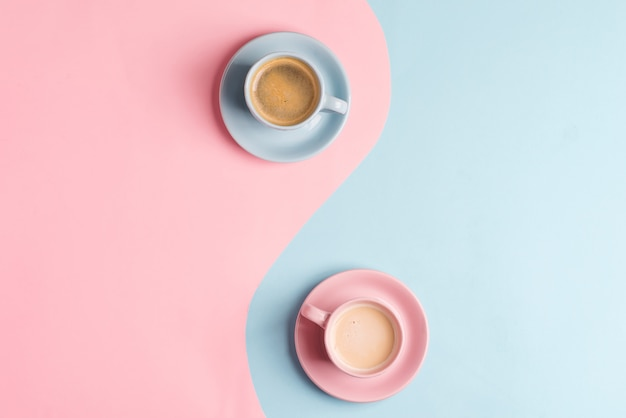 Kreatywny pastelowy niebieski różowy stół z dwiema ceramicznymi filiżankami świeżo parzonego napoju kawowego.