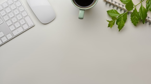 Kreatywny płaski układ obszaru roboczego z klawiaturą komputerową, myszą, filiżanką i liśćmi na stole z miejscem na kopię