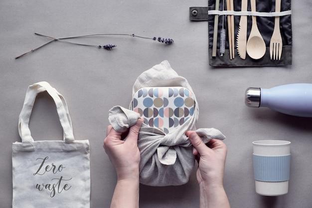 Kreatywny płaski układ, zestaw na lunch bez odpadów, zestaw na wynos na bawełnianej torbie, organizer na bambusowe sztućce, pudełko wielokrotnego użytku i bambusowy kubek.