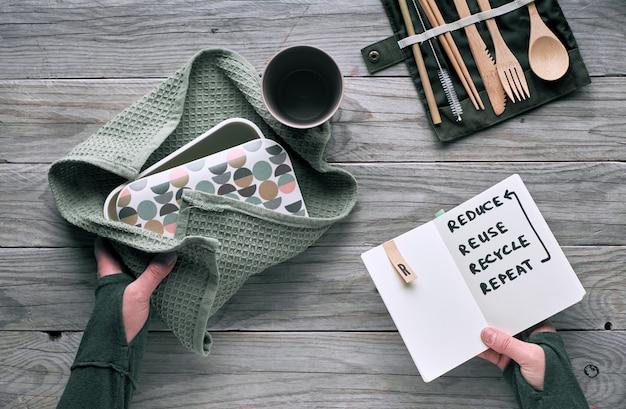 """Kreatywny, płaski, zerowy lunch z zestawem drewnianych sztućców wielokrotnego użytku, pudełkiem na lunch w bawełnianej szmatce i filiżanką kawy wielokrotnego użytku. zrównoważony styl życia, tekst """"zmniejsz, wykorzystaj ponownie, poddaj recyklingowi, powtórz"""" w książce"""