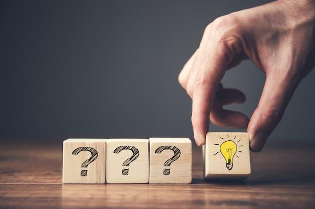 Kreatywny pomysł i innowacja. drewniany sześcian z symbolem znaku zapytania i żarówką