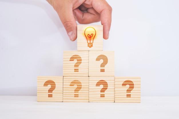 Kreatywny pomysł i koncepcja innowacji. dopasowany drewniany blok z ikoną żarówki na szczycie piramidy i symbolem znaku zapytania