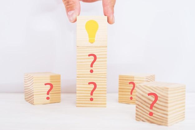 Kreatywny pomysł i koncepcja innowacji. ręcznie wybrany drewniany blok z ikoną żarówki na szczycie piramidy, między innymi ze znakiem zapytania