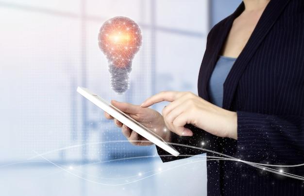 Kreatywny pomysł. koncepcja pomysłu i innowacji. ręka dotykowy biały tablet z cyfrowym hologramem żarówka znak na jasnym tle niewyraźne. koncepcje innowacji, burzy mózgów, inspiracji i rozwiązań.