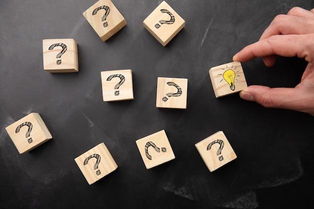 Kreatywny pomysł lub koncepcja innowacji. ręka trzyma drewniany blok z symbolem znaku zapytania i ikoną żarówki