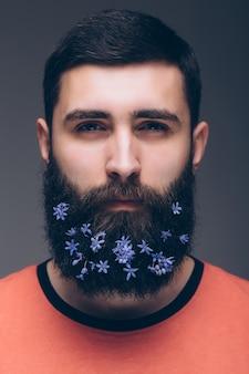 Kreatywny portret młodego pięknego mężczyzny z brodą ozdobioną kwiatami.