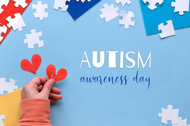 Kreatywny projekt na 2 kwietnia, dzień świadomości świata autyzmu. ręka trzymać papierowy kształt serca