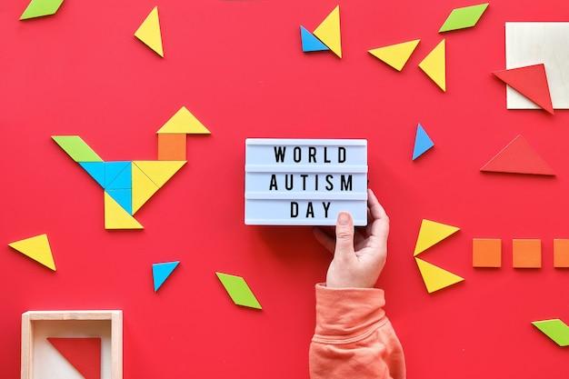 Kreatywny projekt na światowy dzień autyzmu 2 kwietnia, tekst na lightbox. elementy tangram, widok z góry na czerwono
