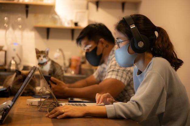 Kreatywny projektant biznesowy, pracujący w odstępach i ubrany w medyczną maskę ochronną aby zapobiec rozprzestrzenianiu się koronawirusa covid-2019, domowe biuro dla małej grupy osób do pracy z domu
