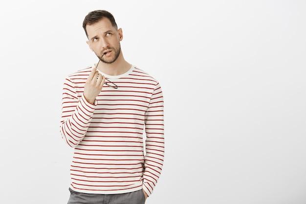Kreatywny przystojny europejczyk, gryzący oprawkę okularów i patrząc w prawy górny róg podczas myślenia lub snu