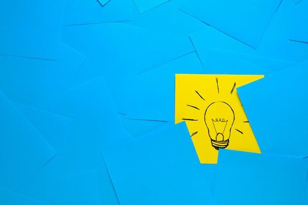 Kreatywny rysunek żarówki na żółtej naklejce, na tle niebieskich naklejek. koncepcja nowych pomysłów, innowacji, rozwiązań problemów.