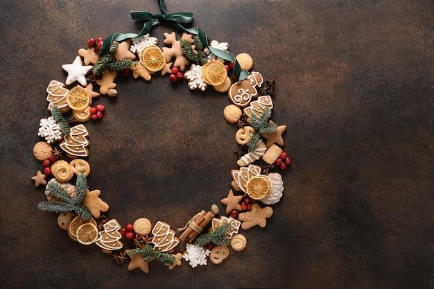Kreatywny słodki świąteczny wieniec z różnych ciasteczek z jagodami na brązowym tle