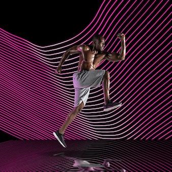 Kreatywny sport na tle ciemnej linii oświetlonej neonem. fitness, sportowiec trening w akcji i ruchu na kolorowych falach. pojęcie hobby, zdrowego stylu życia, młodzieży, akcji, ruchu, nowoczesnego stylu.