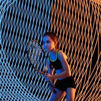 Kreatywny sport na tle ciemnej linii oświetlonej neonem. trening tenisisty w akcji i ruchu na kolorowych falach. pojęcie hobby, zdrowego stylu życia, młodzieży, akcji, ruchu, nowoczesnego stylu.