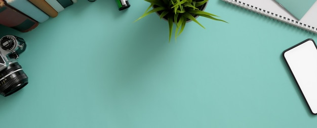 Kreatywny stół roboczy ze smartfonem, aparatem, dekoracją, książkami i kopią miejsca na turkusowym stole