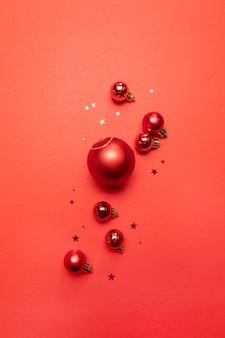 Kreatywny świąteczny plakat z czerwonymi kulkami i brokatem czerwonych gwiazd na czerwono. leżał z płaskim, widok z góry, miejsce