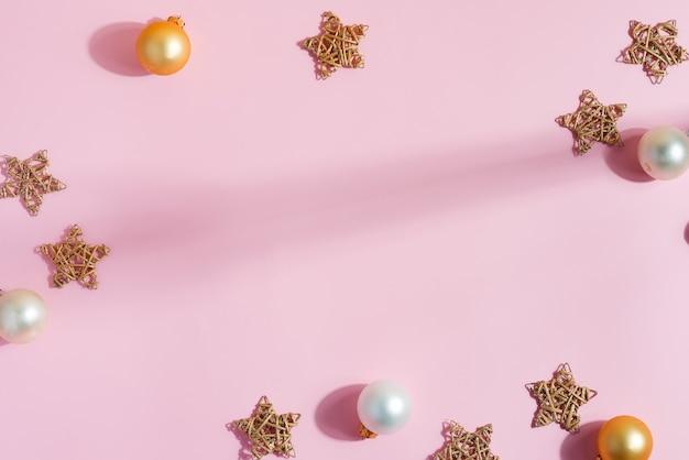 Kreatywny świąteczny płaski układ ręcznie robionych gwiazdek, błyszczących małych złotych i srebrnych kulek na pastelowym różu