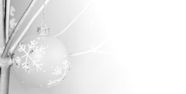 Kreatywny szeroki czarno-biały baner z alternatywnym drzewkiem bożonarodzeniowym z suchego drewna pomalowanego na kolor srebrny i ozdobiony kulką bożonarodzeniową z bliska. skopiuj miejsce na tekst.