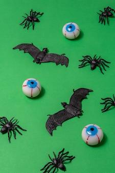 Kreatywny układ halloween z pająkami, nietoperzami i gałkami ocznymi na zielonym tle