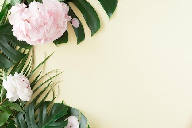 Kreatywny układ i tło z tropikalnych liści palmowych i różowych pastelowych kwiatów. koncepcja lato na żółtym tle. leżał płasko, widok z góry, miejsce.