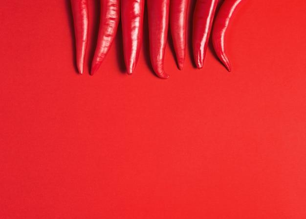 Kreatywny układ papryczki chili na czerwonej powierzchni.