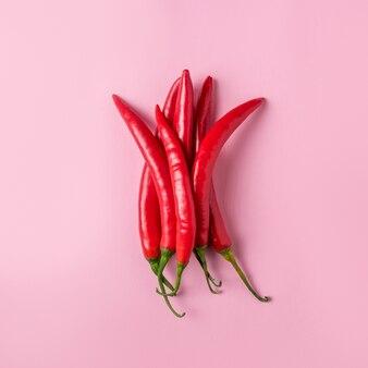 Kreatywny układ papryczki chili na różowej powierzchni.
