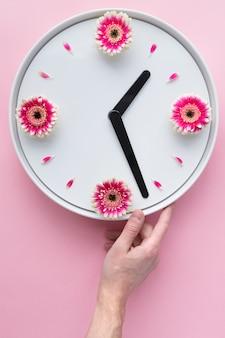 Kreatywny układ ręki mężczyzny trzymającego biały zegar stworzony ze świeżych różowych kwiatów gerbera