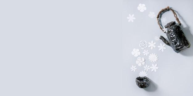 Kreatywny układ transparentu z różnymi białymi papierowymi kwiatami płynącymi z ceramicznego czajnika do filiżanki na szarej ścianie. leżał na płasko, miejsce na kopię. herbata kwiatowa, koncepcja czasu letniego lub wiosennego