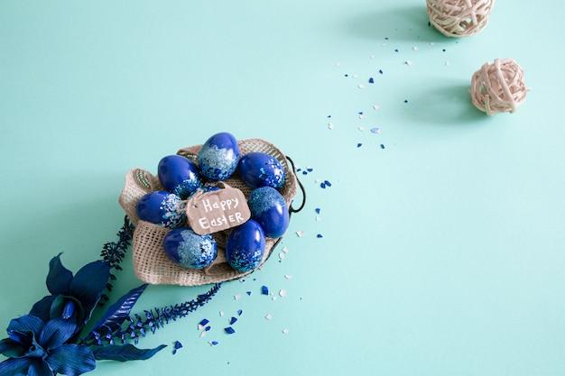 Kreatywny układ wielkanocny wykonany z kolorowych jaj i kwiatów na niebiesko.