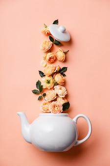 Kreatywny układ wykonany z białej dzbanka do herbaty z różowymi różami w kolorze pomarańczowym