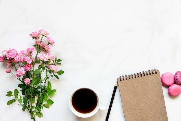 Kreatywny układ wykonany z bukietu różowych kwiatów róży, filiżanki kawy, pustego notatnika i makaroników