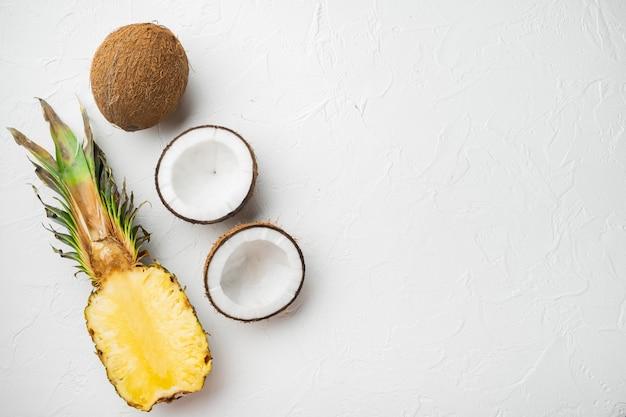 Kreatywny układ wykonany z egzotycznych i tropikalnych owoców, ananasa i kokosa, na tle białego kamiennego stołu, widok z góry płasko leżący, z miejscem na kopię na tekst