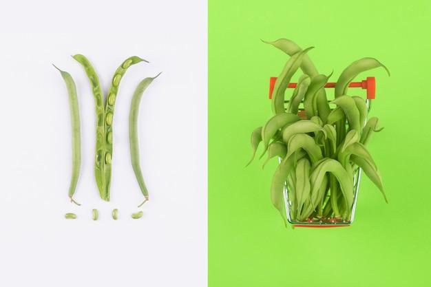 Kreatywny układ wykonany z fasolki szparagowej w koszyku na zielonym tle, kupowanie żywności wegetariańskiej