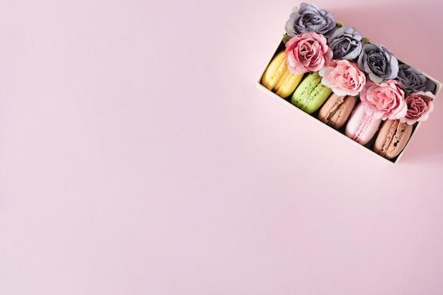 Kreatywny układ wykonany z kwiatów i makaroników.