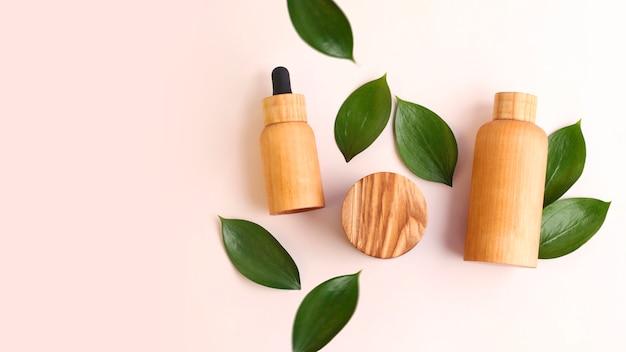 Kreatywny układ z drewnianych pojemników na kosmetyki ze świeżymi zielonymi liśćmi wokół. ładne pastelowe kolory, naturalne materiały. koncepcja ekologiczna. duży baner z miejscem na kopię.