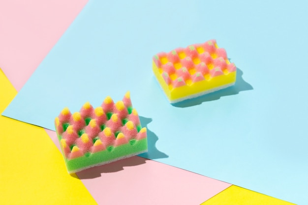 Kreatywny układ z gąbkami do zmywania naczyń na wielokolorowym tle. koncepcja usługi czyszczenia