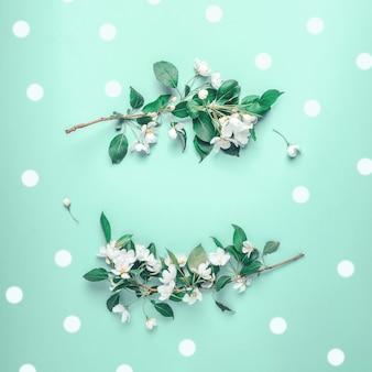 Kreatywny układ z kwitnącą jabłonią na niebieskim tle. leżał na płasko. koncepcja - wiosenny minimalizm