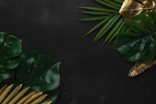 Kreatywny układ ze złotymi i zielonymi liśćmi tropikalnych palm na czarnym tle.