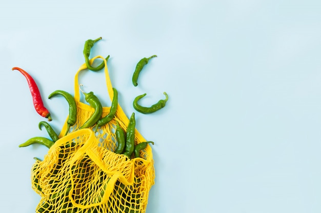 Kreatywny układ zielone papryczki chilli. zielone warzywa w żółtej sznurkowej torbie na pastelowym niebieskim tle. kupa zielonej papryki o nazwie frigitelli