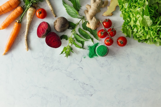 Kreatywny układ żywności z owocami, warzywami i liśćmi na jasnej marmurowej ścianie stołu. minimalna koncepcja zdrowej żywności. leżał na płasko.