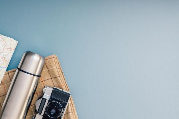 Kreatywny widok z góry na płaską kompozycję na zewnątrz. termos mapa retro aparat sztućce koc szare niebieskie tło kopia przestrzeń.